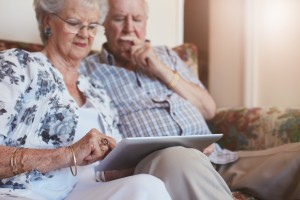 Elderly couple at home using digital tablet